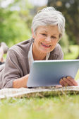 Smiling senior woman using digital tablet at park — Stock Photo