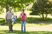 Family of three holding hands at park — Stock Photo