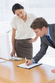 Colleagues with clipboard at office desk — Foto Stock