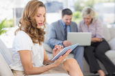Businesswoman using digital tablet with colleagues using laptop — Stock Photo