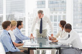 Stern businessman looking down at his staff during a meeting — Stock Photo