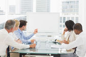 Business people looking at blank whiteboard in conference room — Stock Photo