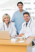 Smiling doctors with laptop at medical office — Stock Photo