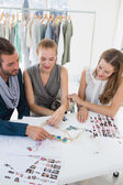 Three fashion designers discussing designs — Stockfoto