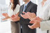 Business team standing in a row applauding — Stockfoto