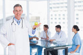Doctor holding apple with group around table at hospital — Stock Photo