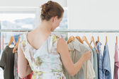 Female customer selecting clothes at clothing rack in store — Stock Photo