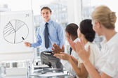 Colleagues applauding businessman after presentation — 图库照片