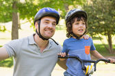 Smiling man with his son riding bicycle — Stockfoto