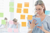 Concentrated artist with digital tablet and colorful sticky note — Stock Photo