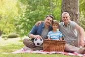 Grandfather, father and son with picnic basket at park — Stock Photo