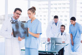 Doctors examining x-ray with colleagues using laptop behind — Stock Photo