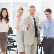 Business team giving thumbs up to the camera — Stock Photo #39200481