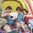 Stock Photo: Family sitting in tent at park