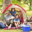 Couple with kids sitting in the tent at park — Stock Photo