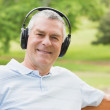 Smiling senior man with headphones at the park — Stock Photo #39201013