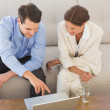 Business partners working on laptop sitting on sofa — Stock Photo
