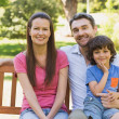 Smiling couple with son sitting on park bench — Stock Photo