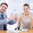 Businessman and woman gesturing thumbs up — Stock Photo