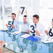 Group of panel judges holding score signs in front of woman — Stock Photo #39202387