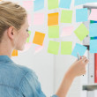 Rear view of a female artist looking at colorful sticky notes — Stock Photo