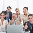 Business colleagues with laptop gesturing thumbs up at desk — Stock Photo #39202831