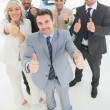 Confident business team gesturing thumbs up — Stock Photo