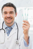 Smiling doctor holding toothbrushes in office — Stock Photo