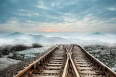 Railway tracks leading to misty mountains — Stock Photo