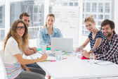 Casual business people around conference table in office — Stock Photo