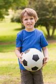 Smiling young boy holding ball in park — Stock Photo