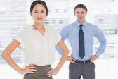 Business colleagues with hands on hips in office — Stock Photo