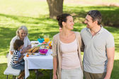 Couple with family dining at outdoor table — Stock Photo