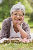 Close-up of a senior woman lying at park — Stock Photo