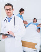 Doctor holding reports with patient and surgeon in background — Stock Photo