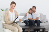 Financial adviser writing notes with couple in background — Stock Photo