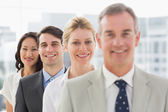 Cheerful business team standing in a line smiling at camera — Stock Photo