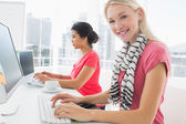 Casual young women using computers in office — Stock Photo