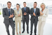 Business team clapping hands together in office — Stock Photo