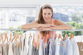 Beautiful female fashion designer with rack of clothes — Stock Photo