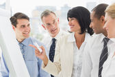 Colleagues watching happy businesswoman pointing to whiteboard — Stock Photo