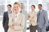 Businesswoman on the phone smiling at camera with team behind he — Stock Photo