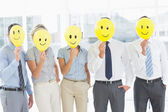 Business people holding happy smiles in front of faces — Stock Photo
