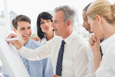 Smiling colleagues watching businessman writing on whiteboard — Stock Photo