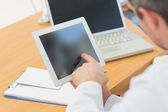 Doctors using laptop and digital tablet in meeting — Stock Photo