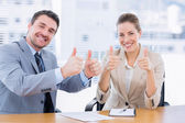 Businessman and woman gesturing thumbs up — Stockfoto