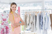 Female fashion designer with rack of clothes in store — Stock Photo