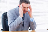 Businessman with severe headache sitting at office desk — Stock Photo