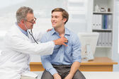 Mature doctor listening to his happy patients chest with stethos — Stock Photo