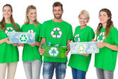 People in recycling symbol t-shirts carrying boxes — Stock Photo